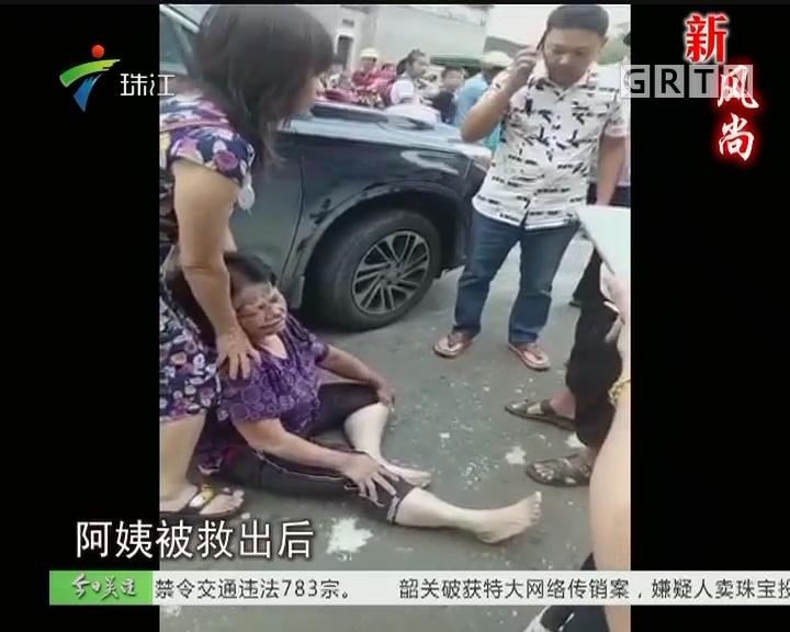 高州:妇女被压车底 市民合力抬车救人