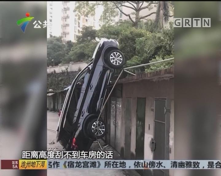 江门:倒车操作失误 汽车跌下平房