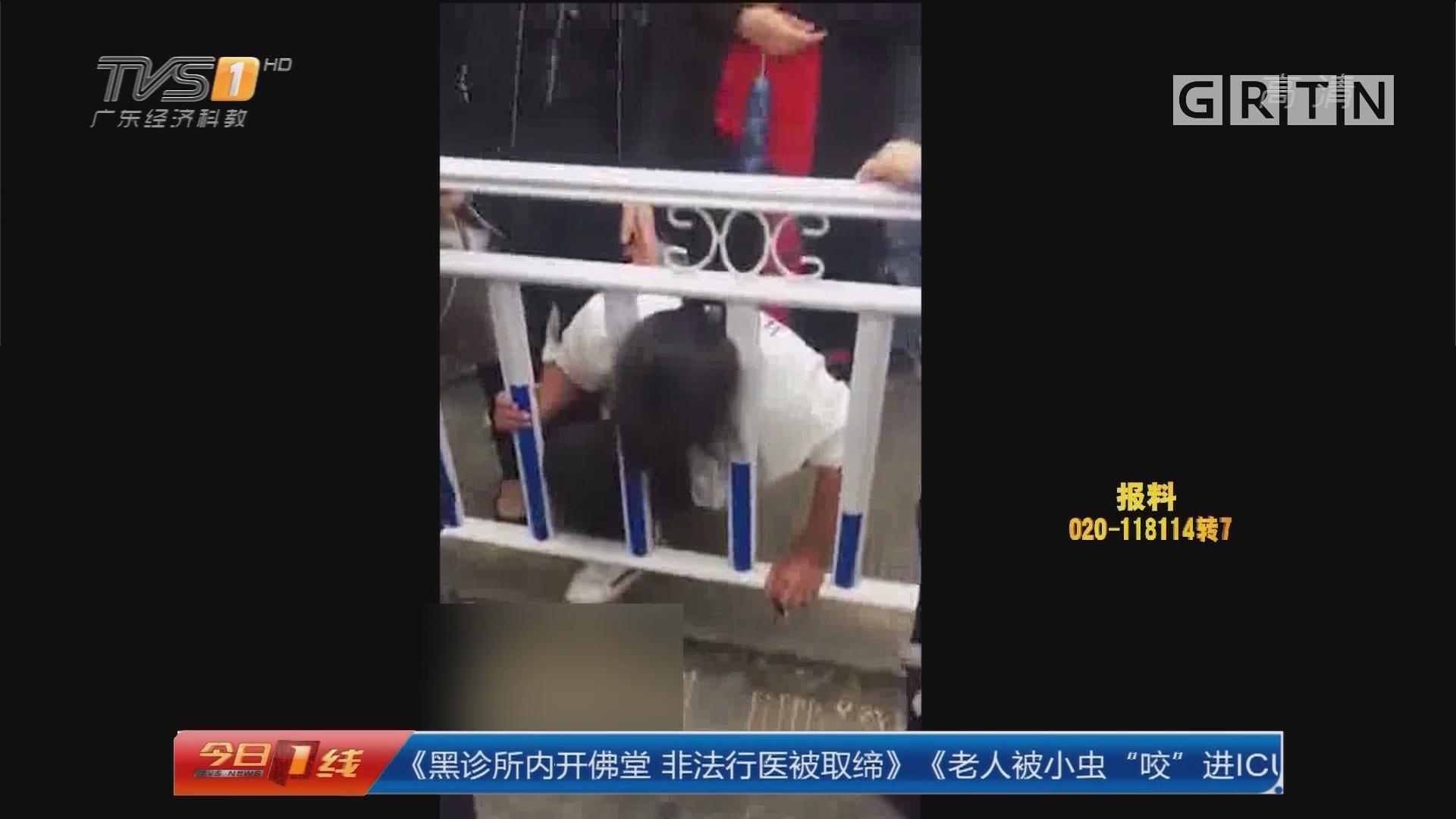 浙江温州:女子翻越隔离护栏头卡栏杆
