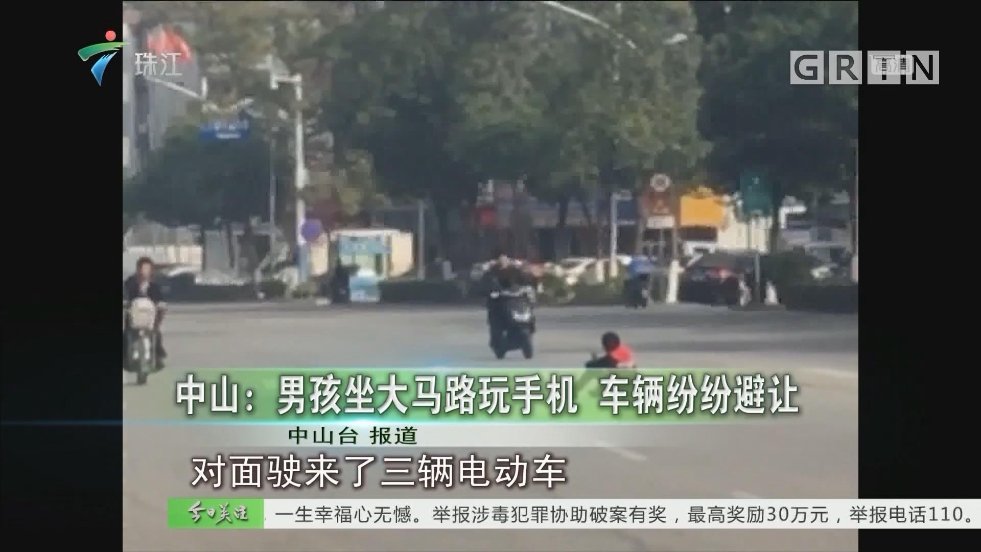 中山:男孩坐大马路玩手机 车辆纷纷避让