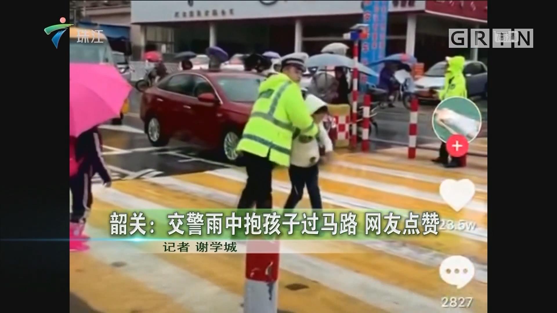 韶关:交警雨中抱孩子过马路 网友点赞