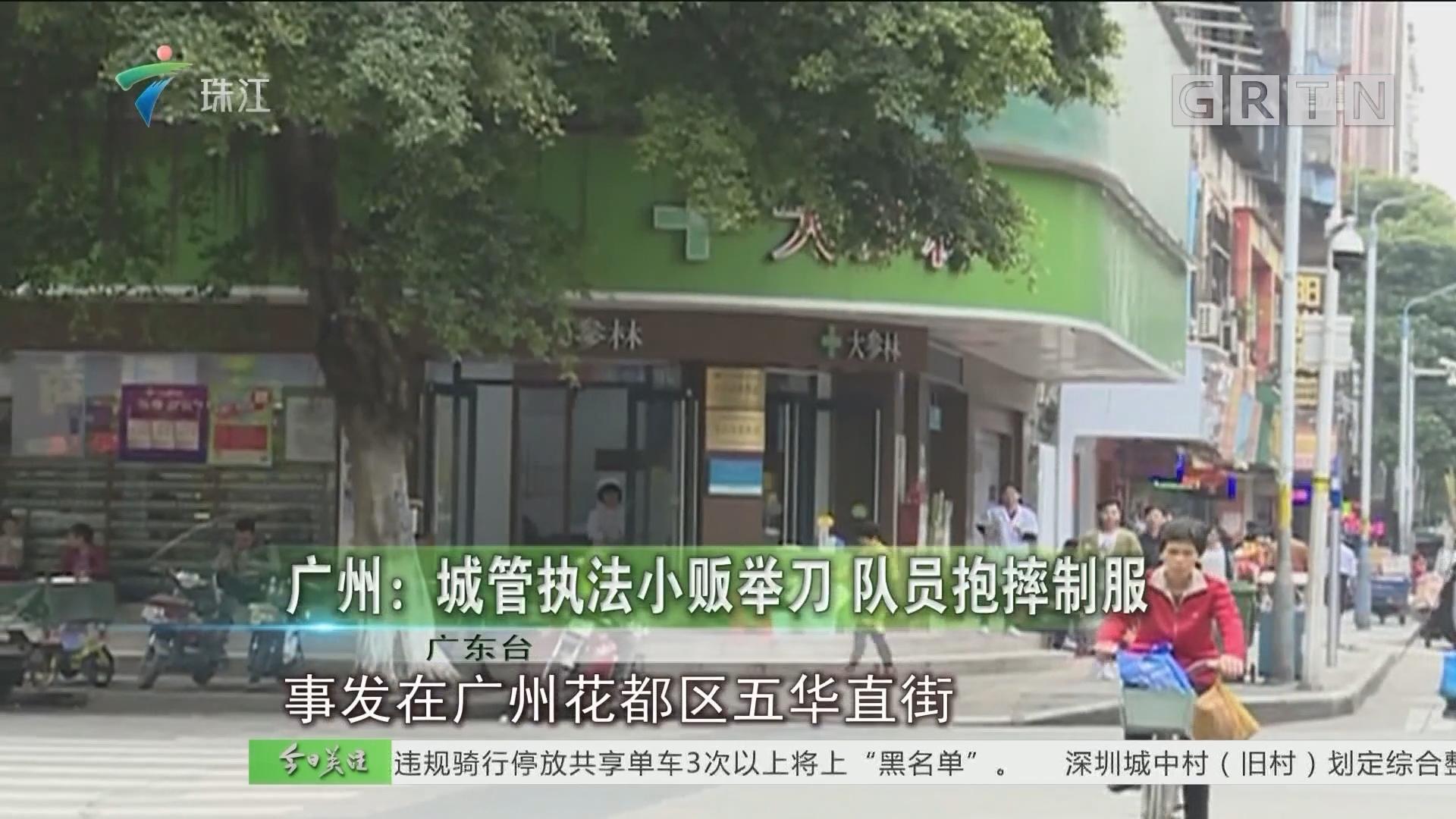 广州:城管执法小贩举刀 队员抱摔制服