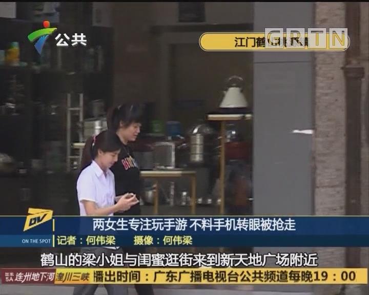 两女生专注玩手游 不料手机转眼被抢走