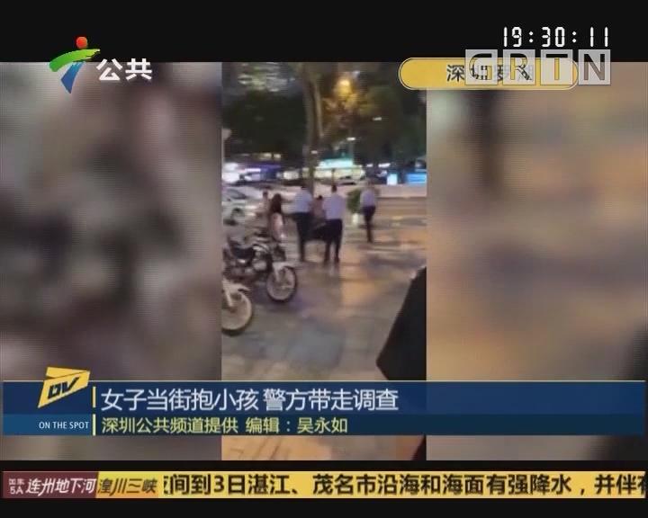 女子当街抱小孩 警方带走调查