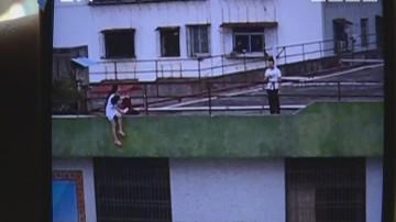 肇庆:女子危坐楼顶挥刀 警方耐心劝服