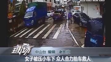 女子被压小车下 众人合力抬车救人