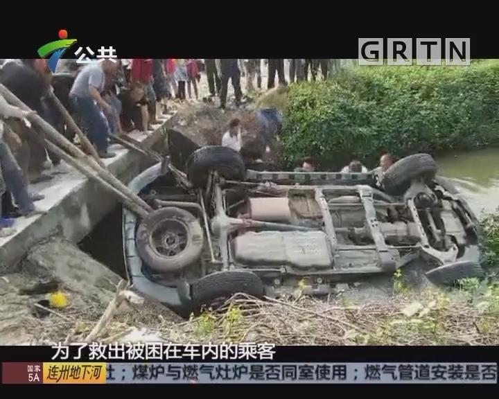 江门:小车冲入水渠 众街坊木棍撑起车身