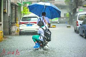 最美背影:广州暴雨中校长蹚水背十多个学生入校