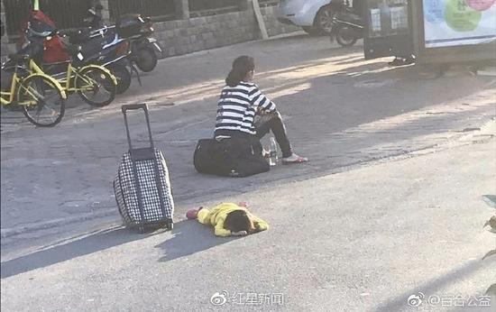 母亲街头踩踏趴地幼女 怼路人:那么好心砸点钱啊