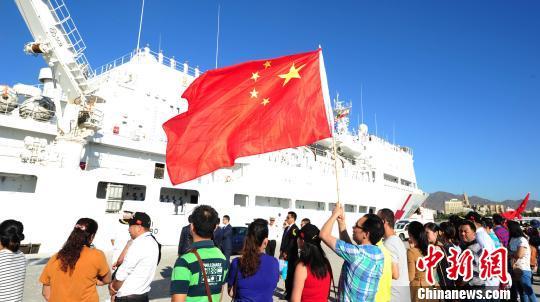 西班牙华人华侨挥动中国国旗,为中国海军和平方舟医院船送行。 江山 摄