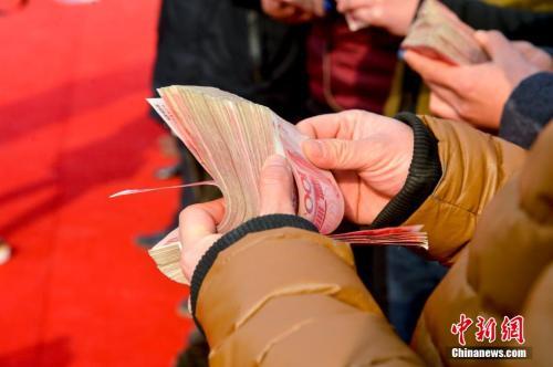 领到钱的农民工正在清点工资。图片来源:视觉中国