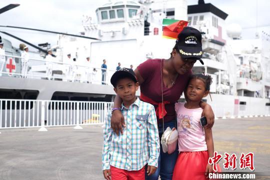11月14日,在马普托港码头,一名莫桑比克妇女带着两个孩子送别和平方舟医院船。 江山 摄