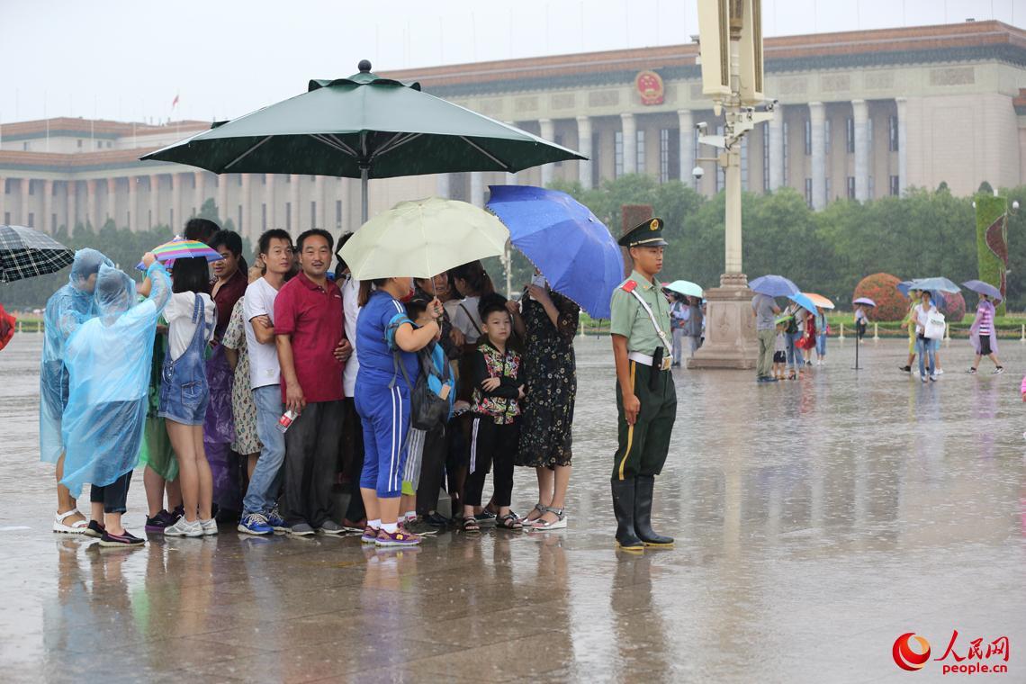 天安门广场执勤哨兵将雨中岗伞让给群众。王彦高摄