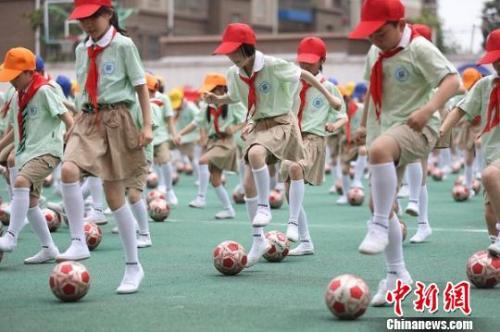 资料图:图为南京一所小学的孩子们正在跳足球操。 泱波 摄
