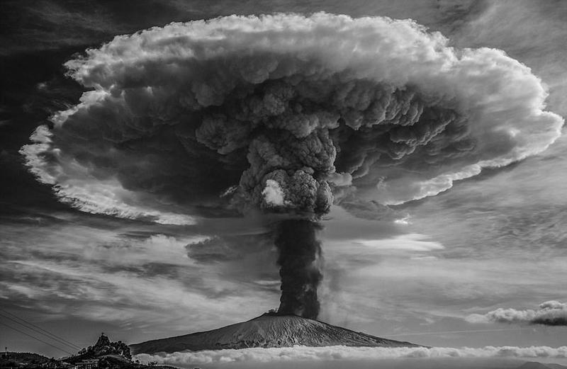 """其中一张名为《埃特纳火山爆发》的照片赢得了评委们的一致好评,被称为""""非凡之作""""。这张照片拍摄到了火山爆发时产生的一朵巨大蘑菇云。从照片来看,一朵巨大的蘑菇云从火山口升腾而起,场面十分壮观。最妙的是,该摄影师将照片处理成黑白照,使得滚滚浓烟犹如层叠堆积的云雾将火山包围其中,而夹杂着火山灰的黑色烟雾则一端与火山相接,一端不断向空中延展,似一棵矗立在仙境中的参天大树,令人心生神往。"""