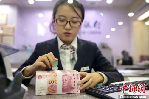 """12月8日,山西太原,银行工作人员清点货币。当日,来自中国外汇交易中心的数据显示,人民币对美元汇率中间价报6.6218,较前一交易日下行23个基点,至此人民币中间价""""十连跌""""。<a target='_blank' href='http://www.chinanews.com/'>中新社</a>记者 张云 摄"""
