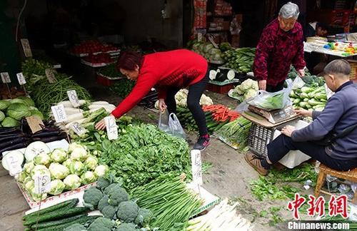 1月10日,中国国家统计局公布的数据显示,2017年12月份中国CPI同比上涨1.8%。从全年数据来看,2017年全年CPI比上年上涨1.6%。图为成都某市场内蔬菜标注的价格,一些民众正在挑选。(资料图) <a target='_blank' href='http://www.chinanews.com/'>中新社</a>记者 刘忠俊 摄