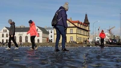 """冰岛池塘水波凝结成奇观 民众玩起""""水上漂"""""""