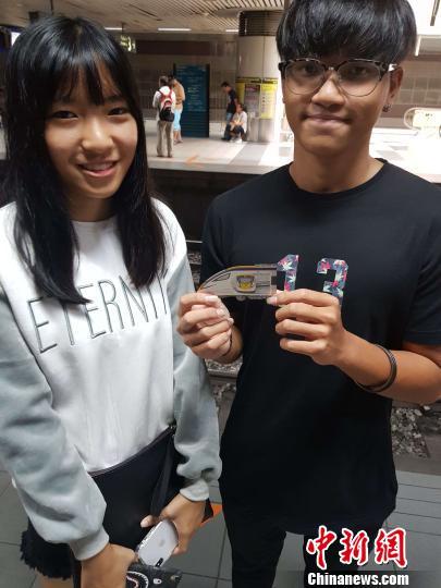 马来西亚华裔情侣手上拿着ETS动车组小全张邮票。中车株机公司供图