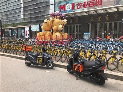 """美团与滴滴外卖""""不相容"""",但有骑手同时在电瓶车上放置了两家的外卖箱。"""
