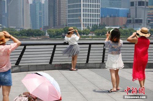 5月16日,游客一身短打行走在上海的街头。当日,上海中心气象台发布了今年第二个高温黄色预警信号。殷立勤 摄