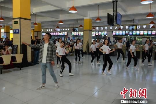 """图为一名男生和众舞蹈演员用""""快闪""""展示中国古典诗词。 崔琳 摄"""