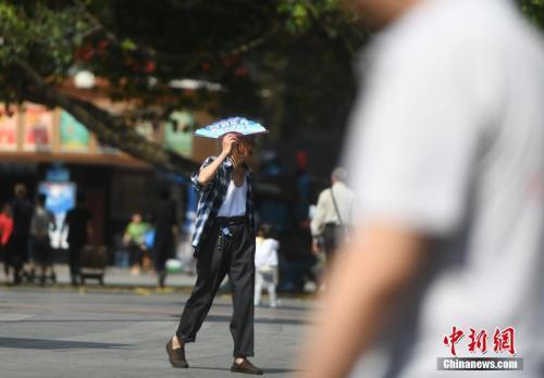"""5月16日,杨家坪步行街上不少市民在高温中出行。当日,重庆市主城区气温飙升,室外温度已经超过35℃,提前进入了""""烘烤""""模式。陈超 摄"""