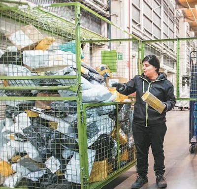 位于智利首都圣地亚哥的智利邮政物流中心,工作人员分拣来自中国的包裹。 豪尔赫摄(新华社发)