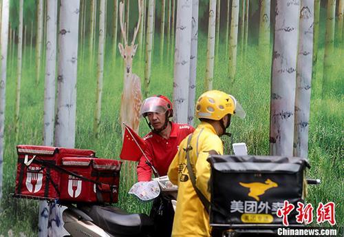 资料图:5月23日,北京西单街头的外卖骑手准备送餐。 <a target='_blank' href='http://www.chinanews.com/'>中新社</a>记者 张宇 摄