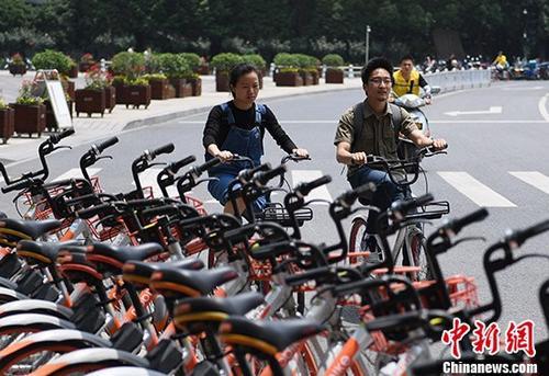 资料图:两名市民正在从摆放的共享单车前骑过。 <a target='_blank' href='http://www.chinanews.com/'>中新社</a>记者王刚摄