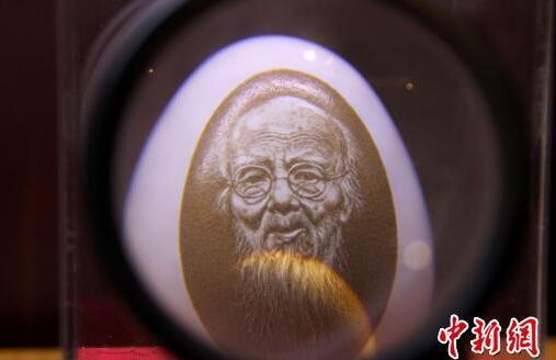 通过放大镜可以看到,在鸡蛋壳上雕刻的人物头像面部表情栩栩如生。 于俊亮 摄