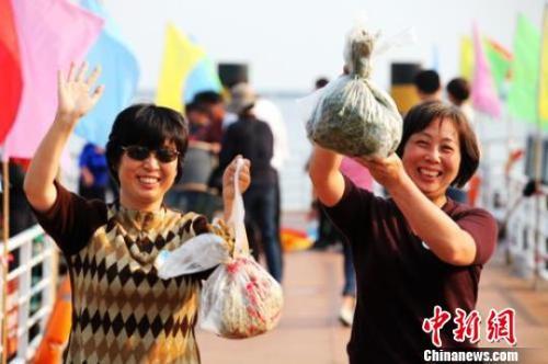 資料圖:兩位女游客手舉獲贈的陽澄湖大閘蟹,開心不已。  李克祥 攝