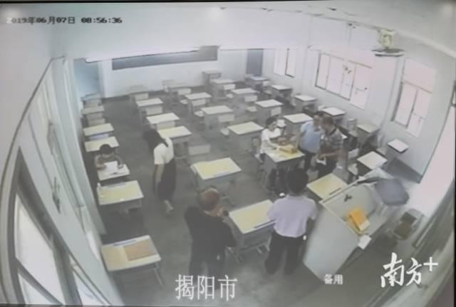 6月7日,在梅峰中学的备用考场里,杨晓婷(右)与另一位特殊考生做好考前准备。 图片由视频监控翻拍。