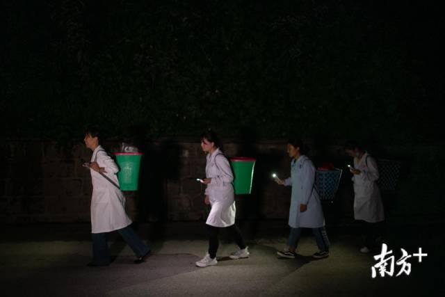 管延萍与其他医生打着手电筒到村里为村民们夜诊。