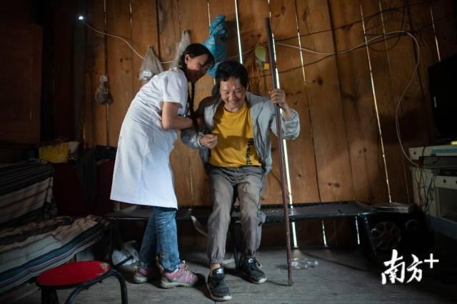 管延萍扶着何宝文,鼓励其独立行走,加强锻炼。