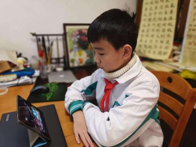 体育东路小学和杨箕小学的学生在家屏幕前上课。杨嘉 摄